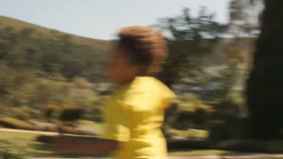 Slow motion of one child running round camera in park.
