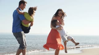 Slow motion of parents twirling children around on beach.