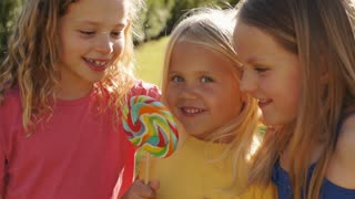 Slow motion of three children licking lolly in park.