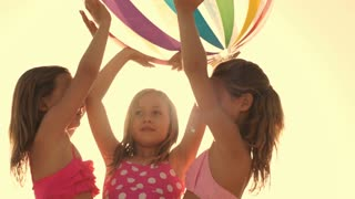 Slow motion of three children playing with beach ball on beach.