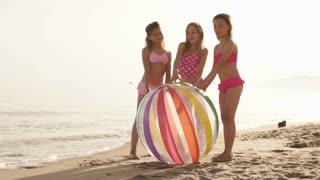 Slow motion of three children pushing beach ball on beach.