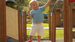 Slow motion of toddler playing on play structure.