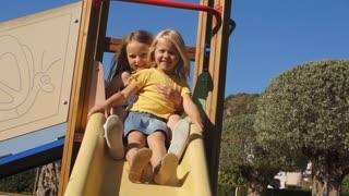 Slow motion of two children on slide in park.