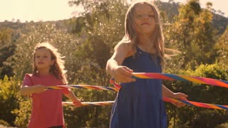 Slow motion of two children playing with hula hoop in park.