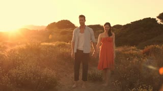 Slow motion of young couple walking on sand dunes in sunset.