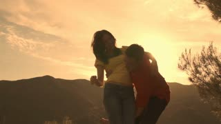 Slow motion shot of couple dancing and twirling overlooking mountain.