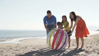 Slow motion shot of family chasing beach ball along beach