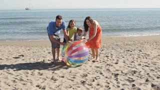 Slow motion shot of family on beach rolling beach ball towards camera.