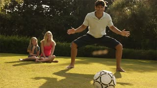 Slow motion shot of family playing soccer.