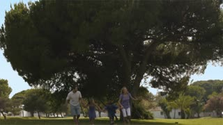 Slow motion shot of family running in park.