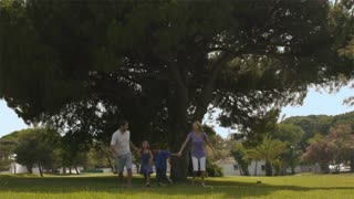 Slow motion shot of family running in park.