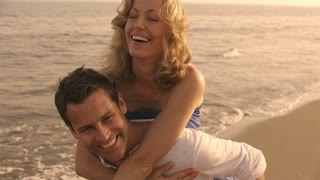 Slow motion shot of playing couple on beach.
