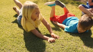 Slow motion shot of two children rolling on grass.