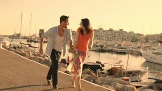 Slow motion shot of young couple running  and dancing by marina in sunset.