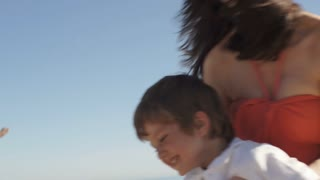 Slow motion woman spinning son around on beach.