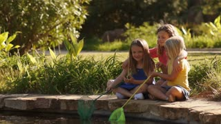 Three children playing with fishing nets by pond in park.