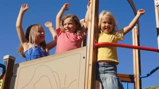 Three children waving on climbing frame in park.