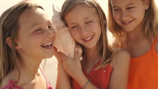 Three girls playing on beach listening to conch shell.