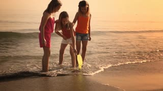 Three girls playing with fishing net in surf.