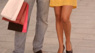 Tilt up shot of couple walking in street with shopping bags