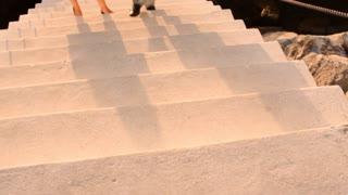 Tilt up shot of couple walking up steps by marina in sunset