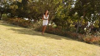 Tilt up shot of woman running towards camera in park