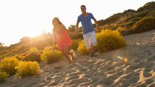 Tilt up shot of young couple running on sand dunes in sunset