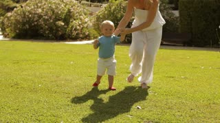 Toddler running with his mother in park.