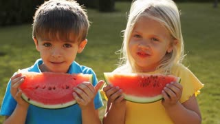 Two children eating water melon in park.