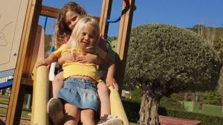 Two children on slide in park.