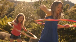 Two children playing with hula hoop in park.