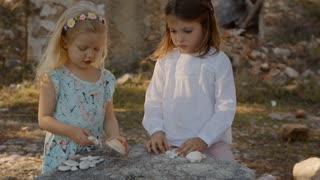 Two children playing with shells and stones