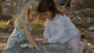 Two children playing with shells