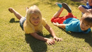Two children rolling on grass in park