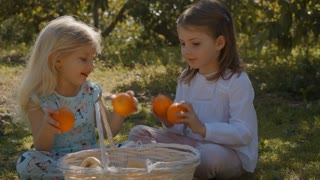 Two children sitting and playing with basket of oranges