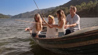 Family fishing from rowing boat on lake