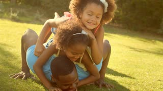 Family in park lying on grass on top of father with two children