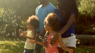 Family in park playing with bubbles