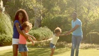 Family in park twirling children around