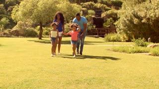 Family running to camera and catching children twirling around