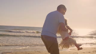 Father and daughter twirling on beach