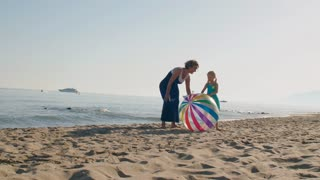 Grandmother and granddaughter on beach running to camera with beach ball