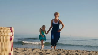 Grandmother and granddaughter on beach running to camera