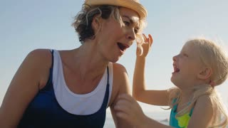 Grandmother and granddaughter sitting on beach playing with hats