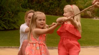 Grandmother and granddaughters playing in park having tug of war