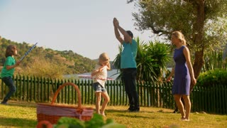 Grandparents and grandchildren or older parents and children playing by lake with hula hoops