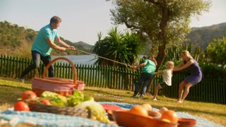 Grandparents and grandchildren or older parents and children playing by lake with rope