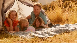 Grandparents and grandchildren or older parents and children playing with tent in countryside