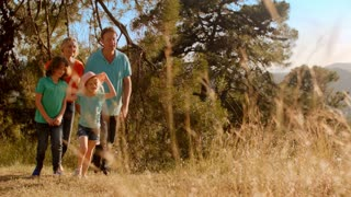 Grandparents and grandchildren or older parents and children walking in countryside