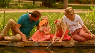 Grandparents and granddaughters playing with fishing nets in park by lake
